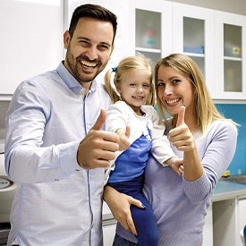 A mother, father, and daughter standing in a dentist's office a giving a thumbs up because they've just seen a family dentist in Ft. Worth