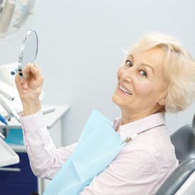 An older woman smiling while sitting in the dentist chair