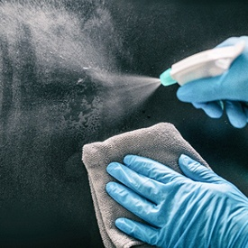 person spraying sanitizer and wiping down a surface with a cloth