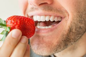 man eating strawberry white teeth