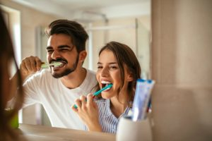 A couple brushing their teeth together.