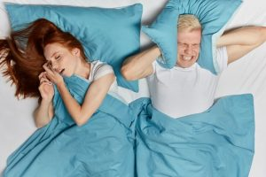 young man upset about woman snoring loudly from sleep apnea