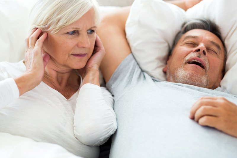 Older man snoring, woman covering her ears